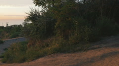 A mountain biker riding a track downhill at sunrise or sunset, slow motion Stock Footage