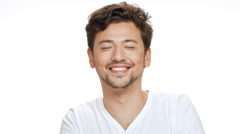 Young handsome man smiling, beckoning, looking at camera over white background Stock Footage