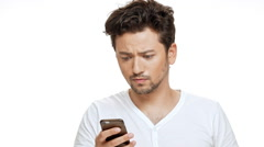 Displeased young handsome man looking at phone over white background. Slow Stock Footage