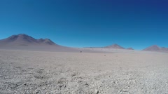 Lonely Silhouette of a Man Walking on a Dry Salt Lake. Salar de Uyuni, Bolivia Stock Footage