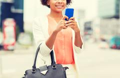 close up of african woman with smartphone in city - stock photo