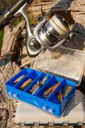 Fishing rod with reel and various kind of baits on the natural background. Stock Photos