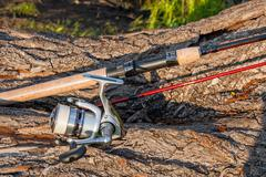 Fishing rod and reel on the natural background. Stock Photos