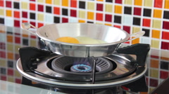Egg Crack And Drop Into An Iron Pan, Where It Starts Frying On A Gas Stove Stock Footage