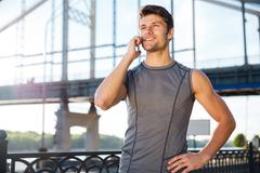 Young man in sports uniform talking on the mobile phone - stock photo