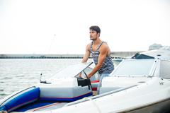 Young handsome man preparing boat to start a journey Stock Photos