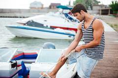 Young handsome man preparing boat to start a journey - stock photo