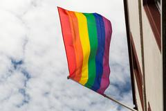 close up of rainbow gay pride flag waving on building - stock photo