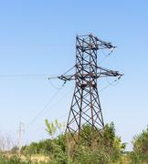 Electricity pylons bearing the power supply across a rural landscape. Stock Photos