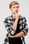 Confident thinking blond handsome young man wearing casual plaid shirt with Stock Photos