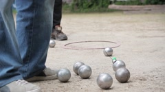 Man Uses Magnetic boule lifter In Petanque Game Stock Footage