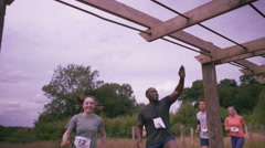 4K Muddy competitors climbing monkey bars at endurance sports contest Stock Footage