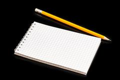 Blank notepad and pencil isolated on black background Stock Photos