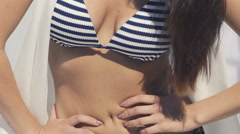 Model in sunglasses and swimsuit looking aside in pose. Slow motion Stock Footage