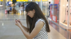 Young woman playing Pokemon GO indoor at shopping center Stock Footage