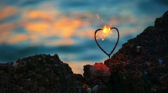Heart shape sparkler firing in front of movins sea waves with spot of warm Stock Footage