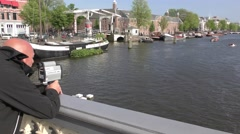 A marine inspector catching speeding boats in Amsterdam canal with a laser gun Stock Footage