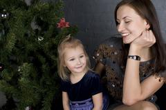 happy family at christmas tree sitting home smiling, together for holiday - stock photo