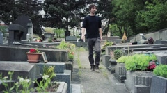 Young Man Walks By Graves In Cemetery Stock Footage