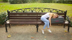 Sad girl sitting on the bench with a suitcase. Stock Footage