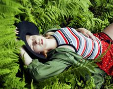 Pretty young blond girl hipster in hat among fern, vacation in green forest Stock Photos