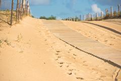Wooden footpath through dunes at the ocean beach Stock Photos