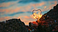 Heart shaped sparkler on the rocky coast in front of slow moving sea water with Stock Footage