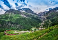 Red train Bernina Express to the passage in the mountains. Stock Photos