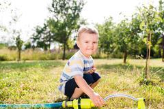 Little boy at the sprinkler having fun, summer garden Stock Photos
