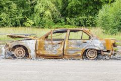 Burned down car wreck on the side of the road - stock photo