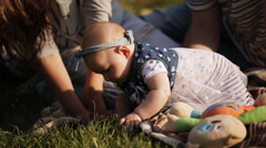 Young couple with a baby resting in the park on the grass Stock Footage