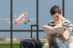 Delayed aeroplane concept. Man is sitting with baggage in airport, waiting fo Stock Photos