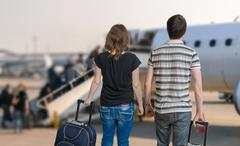 Young couple is travelling on vacation. Man and woman with baggage in airport Stock Photos