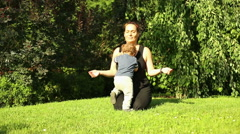 Mother is meditating at the park, little son is hinder Stock Footage