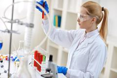 Scientist analyzing reaction of some chemicals. Stock Photos