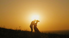 Romantic Silhouette of Man on high hill - at Sunset - kissing and dancing slow - stock footage