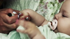Mother cover nails of adorable baby girl by pink lacquer. Manicure. Motherhood - stock footage