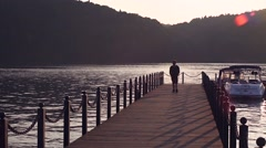 Happy traveler hipster with backpack walking on pier at sunset shore Stock Footage