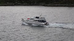 Passing Shot of Small Yacht Motoring through Fjord with Rocky Bank in Background Stock Footage