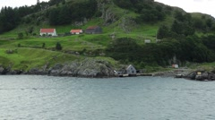 Passing Shot of Red Roof Farm Houses on Rocky Hillside Cliff next to Fjord Stock Footage