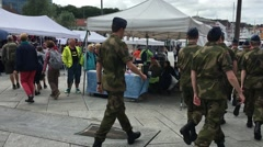 Norwegian Soldiers Walk Past in Open Market with Burger King in Background Stock Footage