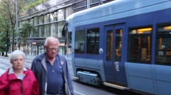 Elderly Couple Pass in Foreground of Approaching Tram on Street in Oslo, Norway Stock Footage