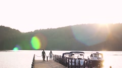 Happy young caucasian family with one year old son walking along wooden jetty Stock Footage