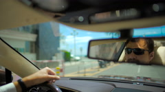 Pleased man in sunglasses driving car and adjusting rear view mirror, vacation Stock Footage