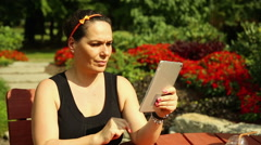 Woman is talking on the Skype on tablet, sitting at the park Stock Footage
