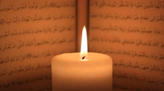 Candle flame burning on Quran arabic text background Stock Footage