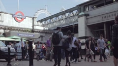 Commuters walk in the shade at London's Embankment Underground station Stock Footage