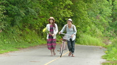 Man pull his red bicycle walking with a lady on the road up to the hill Stock Footage