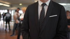 Man in business suit waiting for arrivals in airport hall, travel agent, tourism Stock Footage