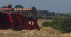 Antique red combine harvester at work in summer wheat field 2K Slow Mo Stock Footage
